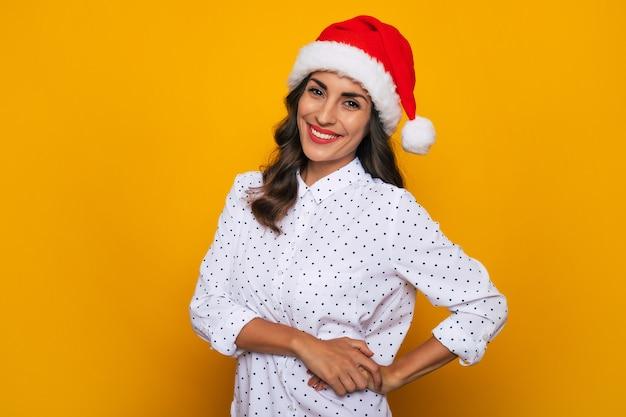 La splendida donna moderna felice e sicura di sé con un cappello da babbo natale rosso e una camicia bianca è in posa sullo sfondo giallo isolato mentre celebra una stagione di natale e capodanno