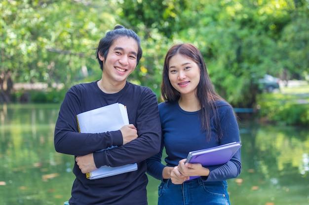 Una splendida coppia di studenti in piedi nel parco di un campus universitario con quaderni e libri in mano, prendendosi una pausa insieme.