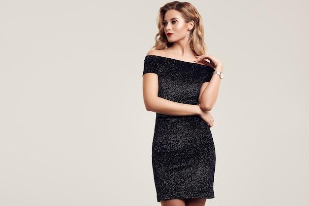 Donna bionda sensuale elegante splendida che porta il vestito nero da modo
