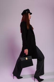 Splendida giovane donna elegante con berretto vintage nero in cappotto lungo nero alla moda in pantaloni a righe in stivali tacco alto con borsa in pelle in posa al chiuso. modello di ragazza moderna. studio fotografico fresco.