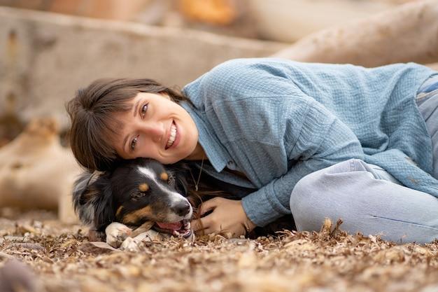 Splendida ragazza dalla pelle chiara sdraiata sul suo cane sulla spiaggia con un sorriso
