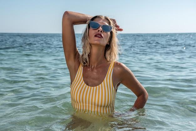 Splendida modella in posa nel mare calmo.