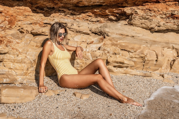 Splendida modella in posa su una spiaggia rocciosa.