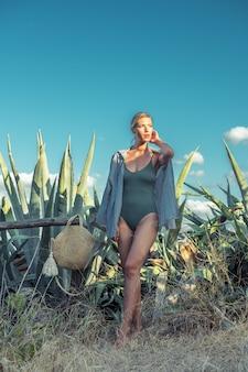 Splendida modella in costume da bagno su uno sfondo di cactus.