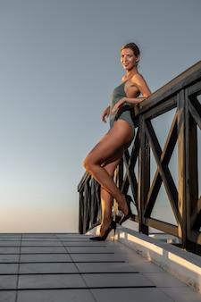 Splendida modella in costume da bagno in posa su un piccolo ponte.