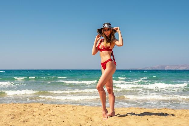 Splendida modella in costume da bagno su una spiaggia di sabbia.