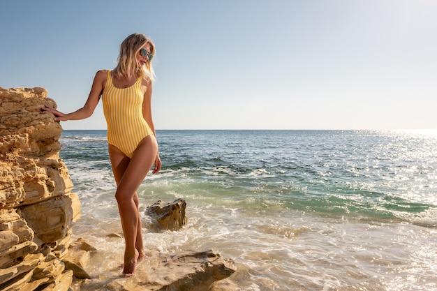 Splendida modella su una spiaggia rocciosa tropicale.