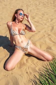 Splendida modella con foglia di palma in posa su una spiaggia di sabbia