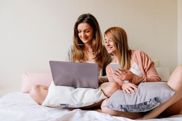 Bellissimi amici che usano il portatile in camera da letto. il concetto di migliore amico.