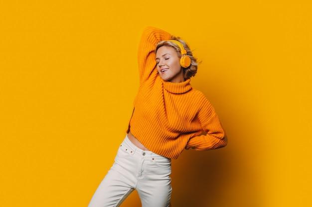 Una splendida ragazza che ascolta musica ed è completamente isolata dal nostro mondo con le sue cuffie gialle e la musica affascinante in sottofondo