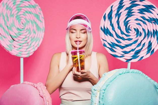 Splendida ragazza con capelli biondi che indossa top e berretto rosa in piedi con enormi dolci lecca-lecca in rosa