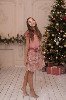 Splendida ragazza con un regalo di natale per le vacanze in interni eleganti.