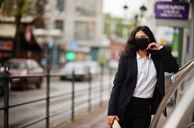 La splendida donna indiana indossa una maschera formale e nera, in posa in strada durante la pandemia covida.