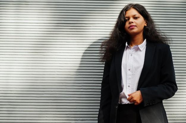Splendida donna indiana indossare posa formale contro il muro grigio.