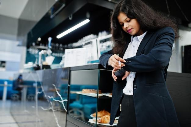 Splendida donna indiana indossare posa formale al caffè vicino al bancone del bar.