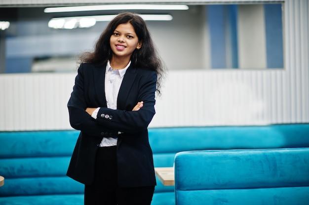 Splendida donna indiana indossare posa formale al caffè.
