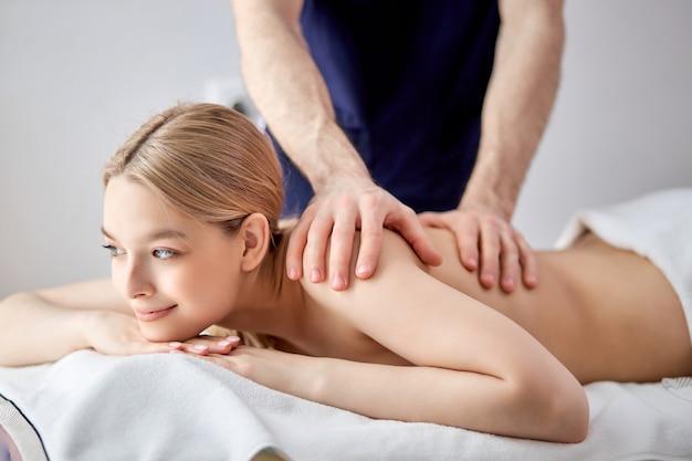 Splendida signora sdraiata sulla pancia che riceve un massaggio sulla schiena da un ragazzo caucasico terapista maschio ritagliato in bl...