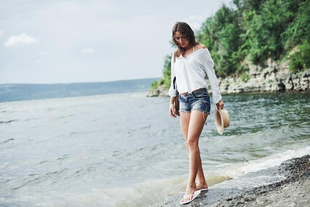Splendida ragazza modello in posa sulla spiaggia con sfondo scogliera con alberi.