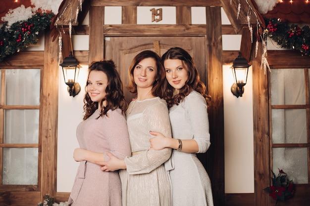 Splendida madre e le sue due figlie in abiti da sera e tacchi alti sedute vicine l'una all'altra sulla soglia