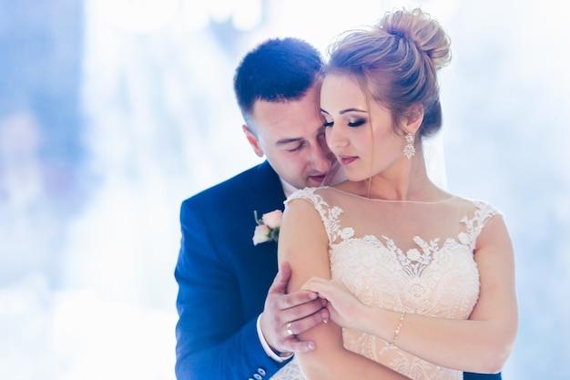 Splendidi sposi ballano un ballo di nozze. sala ristorante con luci e fumo.