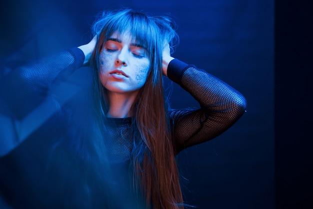 Persona splendida. studio girato in studio scuro con luce al neon. ritratto di giovane ragazza