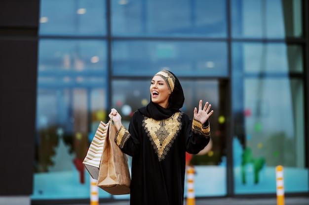 Splendida donna musulmana sorridente positiva in abbigliamento tradizionale in piedi davanti al centro commerciale con le borse della spesa in mano le mani salutando un amico.