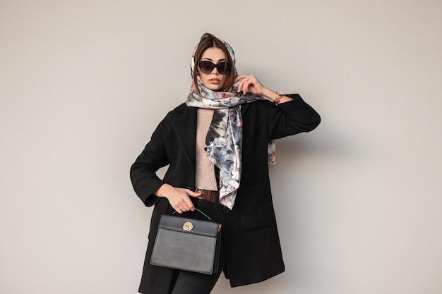 Splendida donna professionale piuttosto giovane in eleganti occhiali da sole in cappotto nero alla moda con borsa in pelle con una sciarpa vintage sulla testa in posa vicino a un muro all'aperto. modello di moda della ragazza di affari. signora sexy.