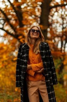 Splendida modella bella giovane donna in bellissimo cappello di paglia in elegante abito a righe in occhiali da sole rotondi alla moda si trova sulla strada il giorno d'estate. la ragazza sexy in vestiti eleganti gode del sole all'aperto.
