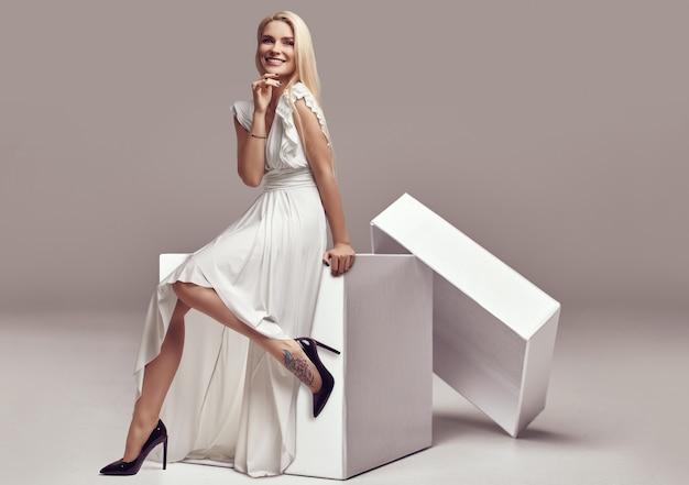 Donna bionda sensuale splendida in vestito bianco in una grande scatola di acquisto