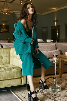 Modello castana sensuale splendido in vestito di modo che si rilassa con il narghilé