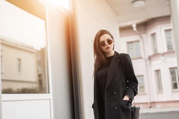 Splendida giovane donna sexy in bella giacca nera in t-shirt vintage in eleganti occhiali da sole si trova vicino all'edificio bianco al tramonto. modello di moda ragazza americana piuttosto alla moda in giornata di sole all'aperto.