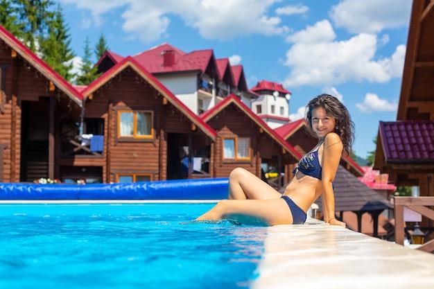 Una splendida ragazza magra rilassarsi in piscina in una calda giornata estiva.