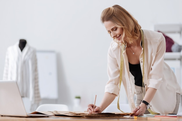 Splendida donna designer sorridente che indossa un metro a nastro sul collo e prende appunti sui modelli di vestiti mentre ha un manichino con una camicia sullo sfondo.