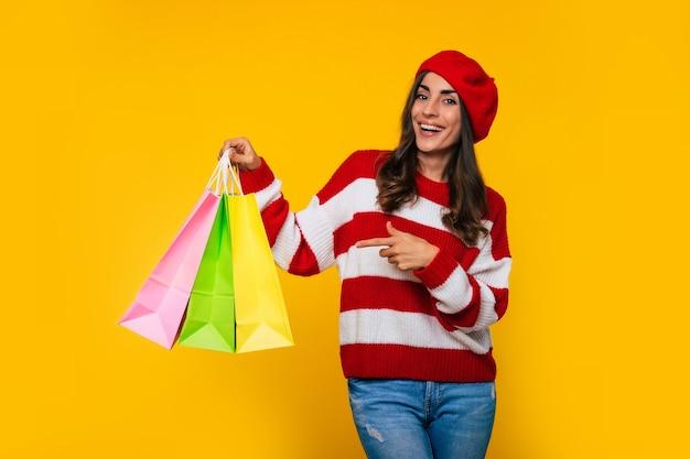 Splendida donna alla moda in un maglione a righe e berretto rosso con molte borse della spesa colorate in mano è in posa isolato su sfondo giallo