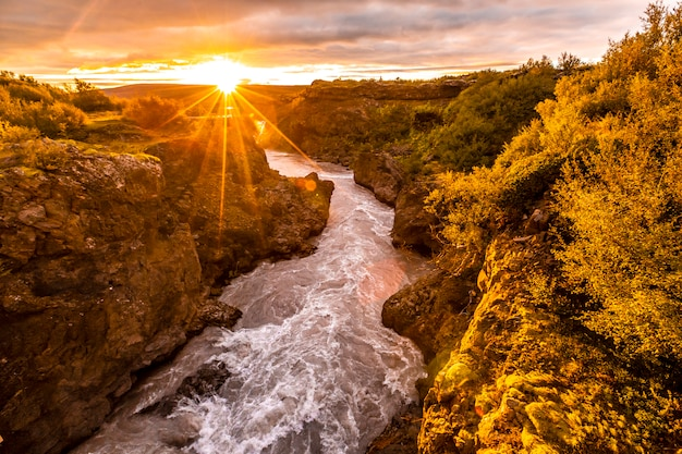 Tramonto splendido sul ponte di legno del fiume barnafoss, islanda