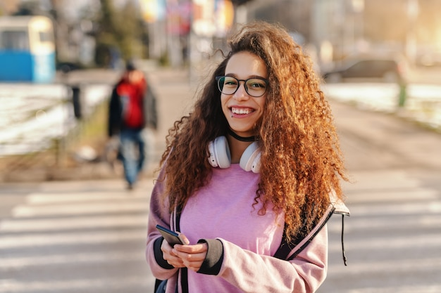 Adolescente splendido con il sorriso a trentadue denti e le cuffie intorno al collo facendo uso dello smart phone sulla via.