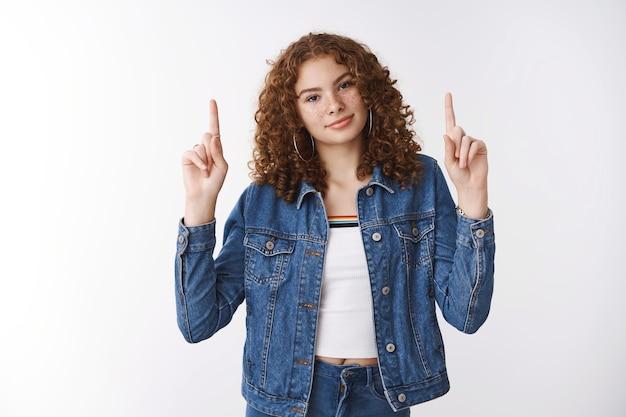 Splendida adolescente rossa ragazza postacne cicatrici sorridente fiducioso amichevole alzare le dita indice puntare verso l'alto promuovere la positività del corpo indisturbati difetti personali concetto di cura di sé, in piedi sfondo bianco
