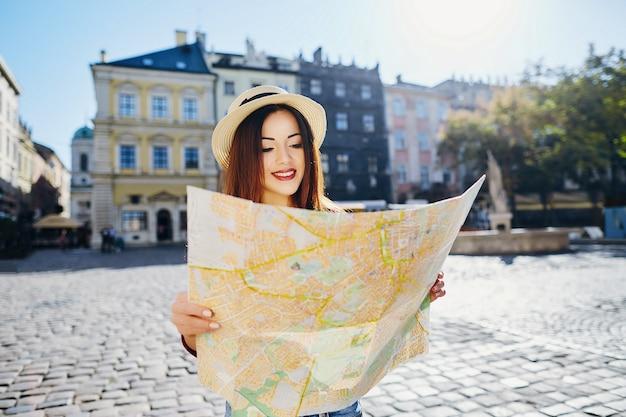 Splendida ragazza turistica con capelli castani che indossa cappello e camicia rossa, che tiene la mappa sullo sfondo della città europea vecchia e sorridente, viaggiando.