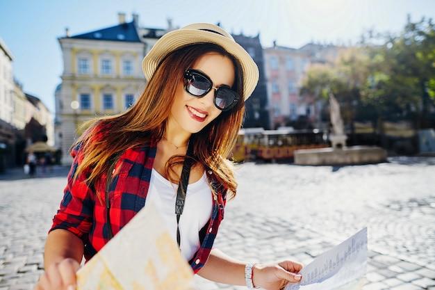 Splendida ragazza turistica con capelli castani che indossa cappello, occhiali da sole e camicia rossa, che tiene la mappa al vecchio sfondo della città europea e sorridente, in viaggio, ritratto.