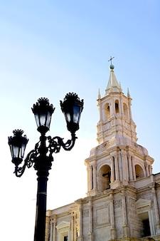 Splendido campanile in pietra vulcanica bianca della basilica cattedrale di arequipa con lampione in ferro nero vintage, arequipa, perù