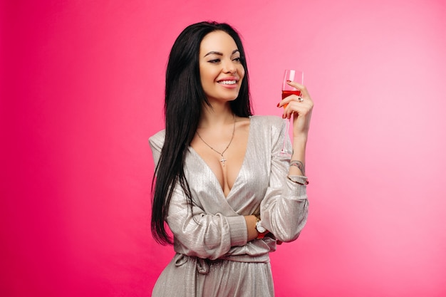 Donna splendida in abito da cocktail con un bicchiere di champagne.