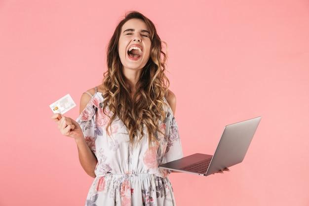 Donna splendida in vestito che tiene laptop d'argento e carta di credito, isolata sul rosa