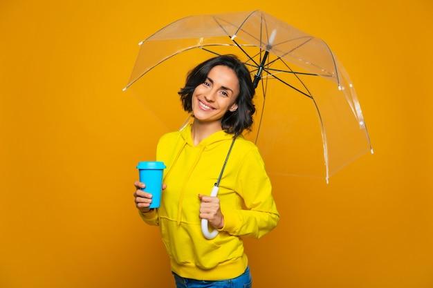 Splendida donna. splendida donna con un ampio sorriso sul viso sotto un ombrello trasparente, con una tazza blu nella mano destra, vestita con una felpa gialla.