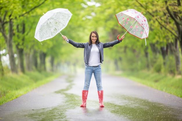 Una donna splendida si trova su una strada asfaltata piovosa nella natura tenendo due ombrelli con le braccia spalancate.