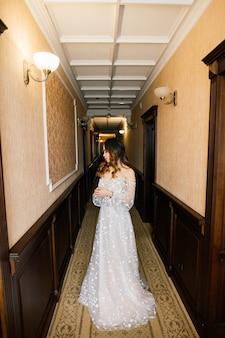 Splendida giovane donna asiatica in abito elegante che guarda l'obbiettivo e la finestra, la mattina della sposa, matrimonio