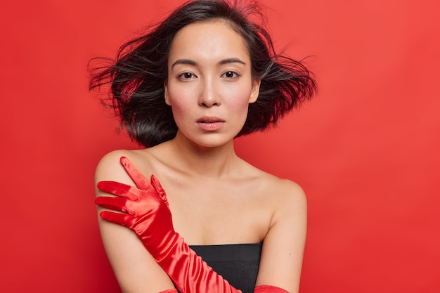 Splendida giovane donna asiatica con i capelli scuri che fluttuano nell'aria guarda seriamente la telecamera indossa un elegante abito nero guanti lunghi in piedi spalle nude ha una pelle sana isolata sul muro rosso