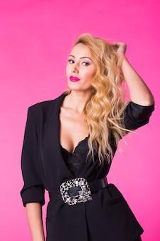 Splendida giovane donna bionda in vestiti alla moda alla moda neri in posa su sfondo rosa.