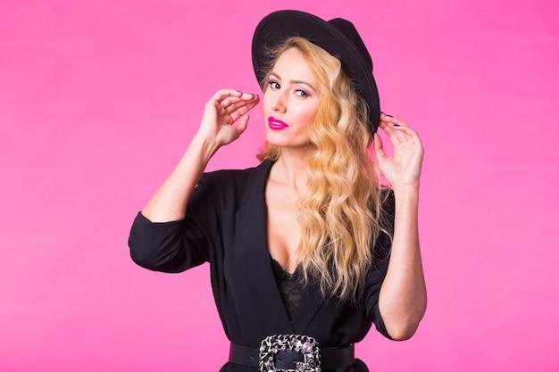 Splendida giovane donna bionda in cappello nero alla moda alla moda in posa su sfondo rosa.