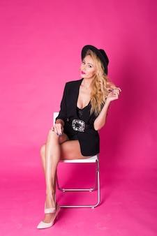 Splendida giovane donna bionda in cappello nero alla moda alla moda in posa sulla parete rosa