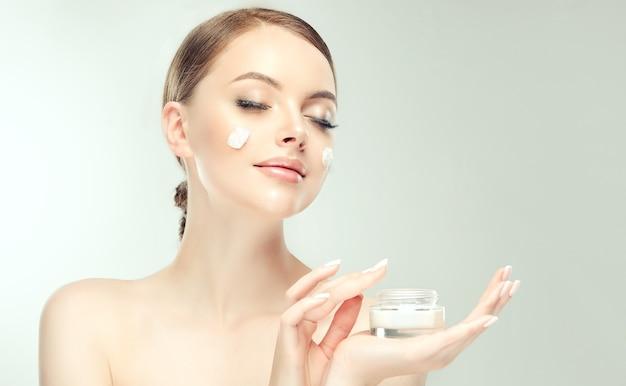 Bellissima, giovane, donna dai capelli castani con macchie di crema cosmetica sulla pelle ben curata